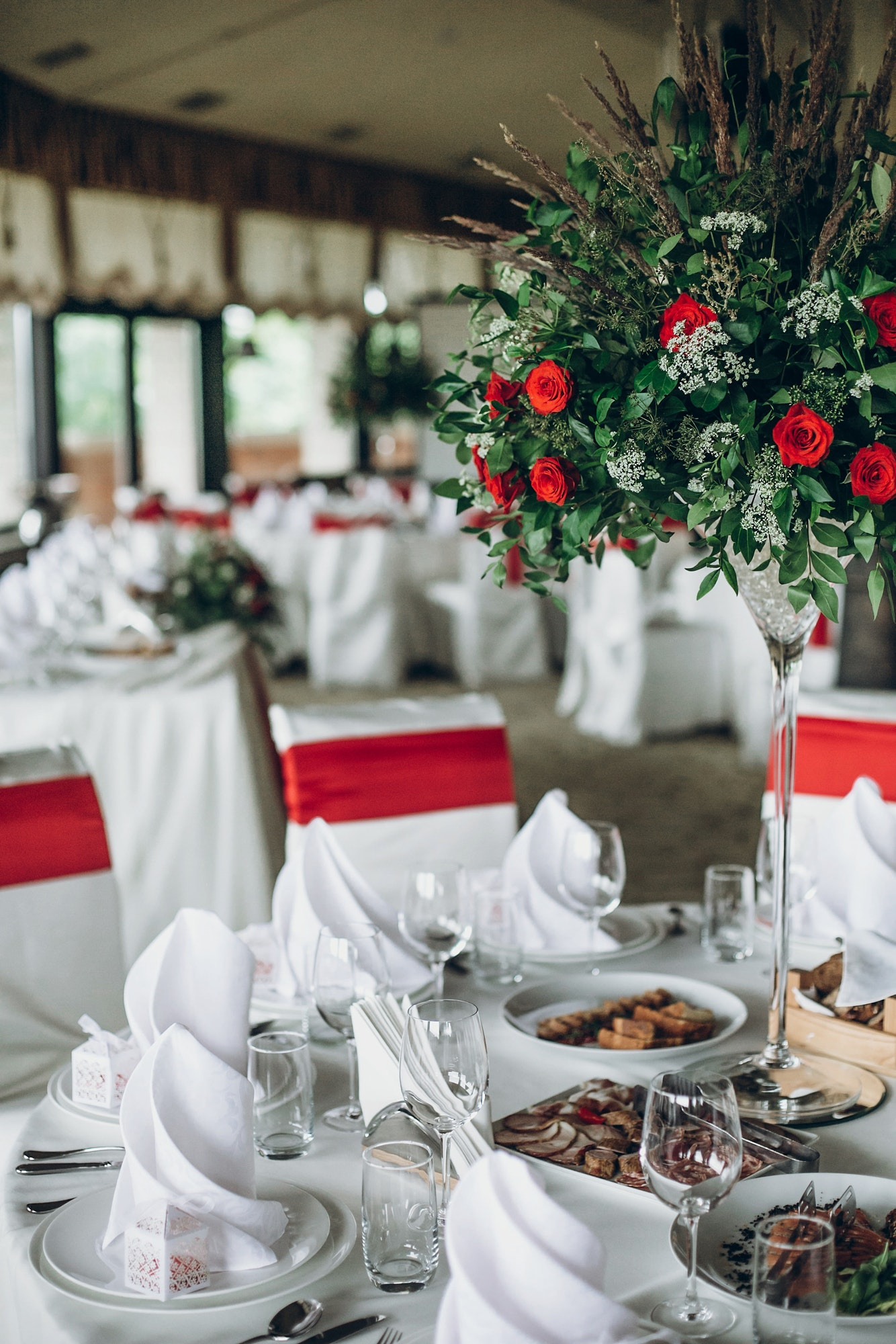 Wedding table with food, silver cutlery, empty glasses, white silk chairs and napkins